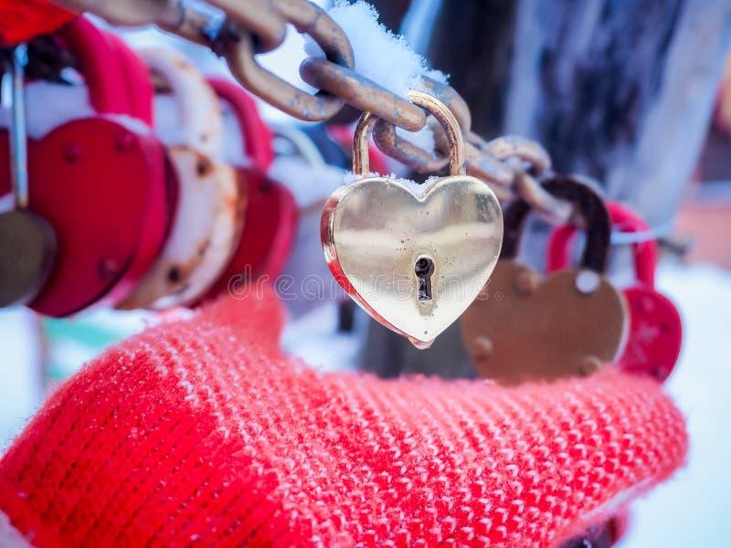 Guanto femminile della mano che giudica lucchetto dorato nella forma di cuore all'aperto nell'orario invernale immagine stock