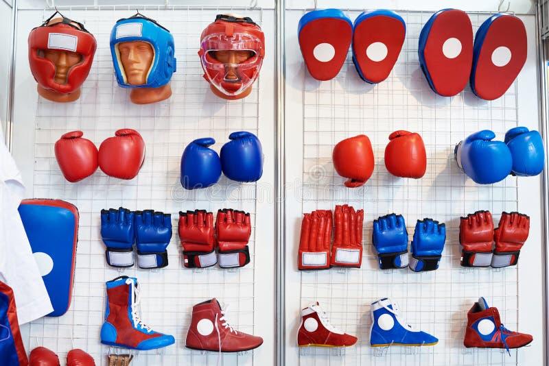 Guantoni da pugile, caschi e scarpe per le arti marziali in negozio immagini stock