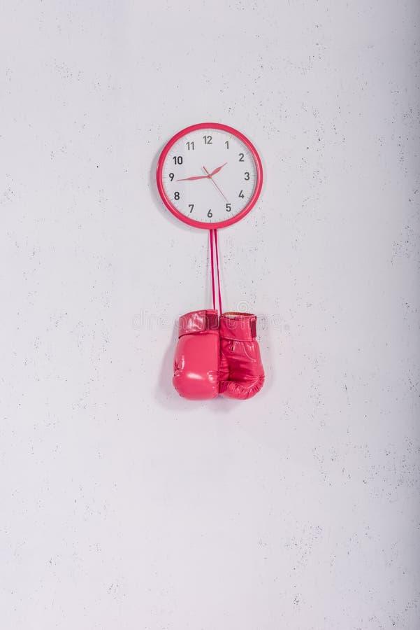 guantoni da pugile rosa che appendono all'orologio di parete rosa su bianco immagini stock libere da diritti