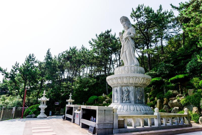Guanyin or Guan Yin Goddess of Mercy white stone statue at Haedong Yonggungsa Temple. Guanyin or Guan Yin Goddess of Mercy white stone statue on the top of the royalty free stock photo