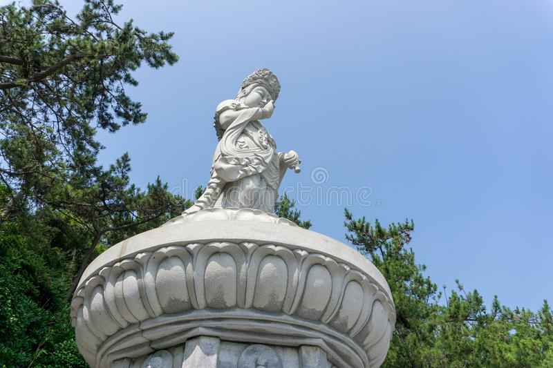 Guanyin or Guan Yin Goddess of Mercy white stone statue on the top of the hill at Haedong Yonggungsa Temple. BUSAN, SOUTH KOREA - JULY 20, 2017 : Guanyin or Guan royalty free stock image