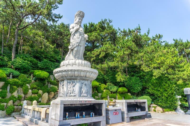 Guanyin or Guan Yin Goddess of Mercy white stone statue on the top of the hill at Haedong Yonggungsa Temple. BUSAN, SOUTH KOREA - JULY 20, 2017 : Guanyin or Guan royalty free stock photo