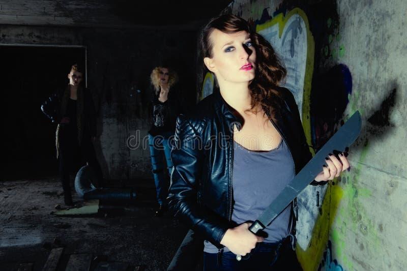 Guard brunette. Self-confident guard brunette has equipped with a machete, horizon format stock photo