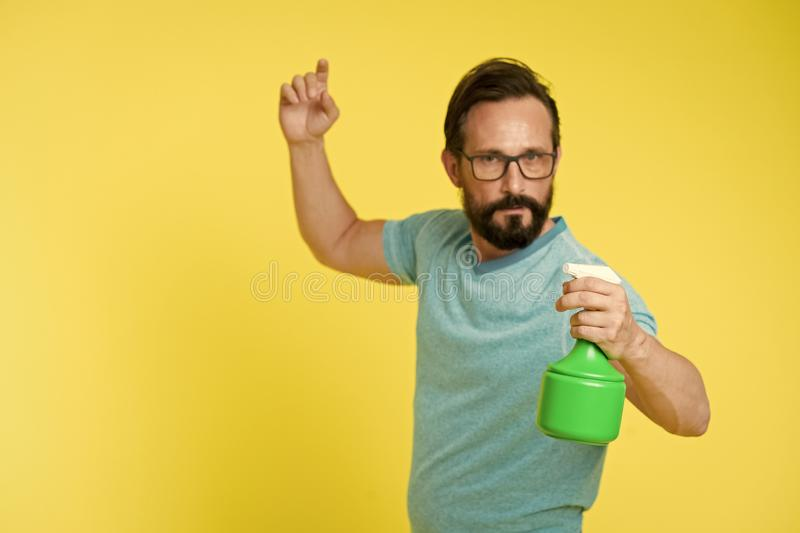On guard of freshness. Refresh concept. Bearded man with eyeglasses refresh sprinkling water. Man refresh with spray. Bottle yellow background. Time to refresh stock photos
