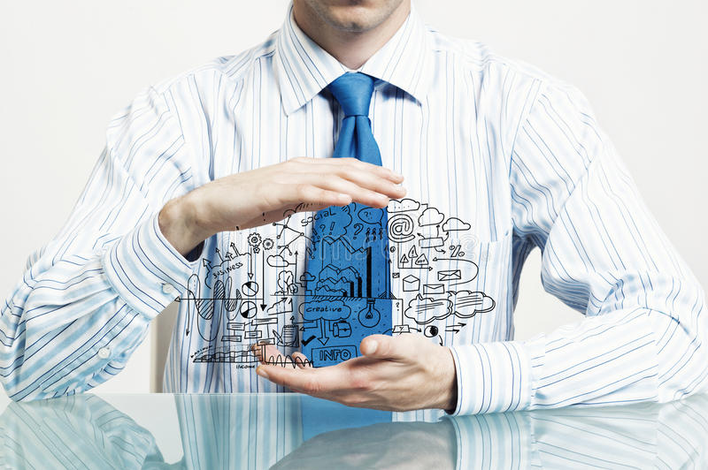 Guard of his ideas. Businessman hand protecting business idea sketch with palms stock photography
