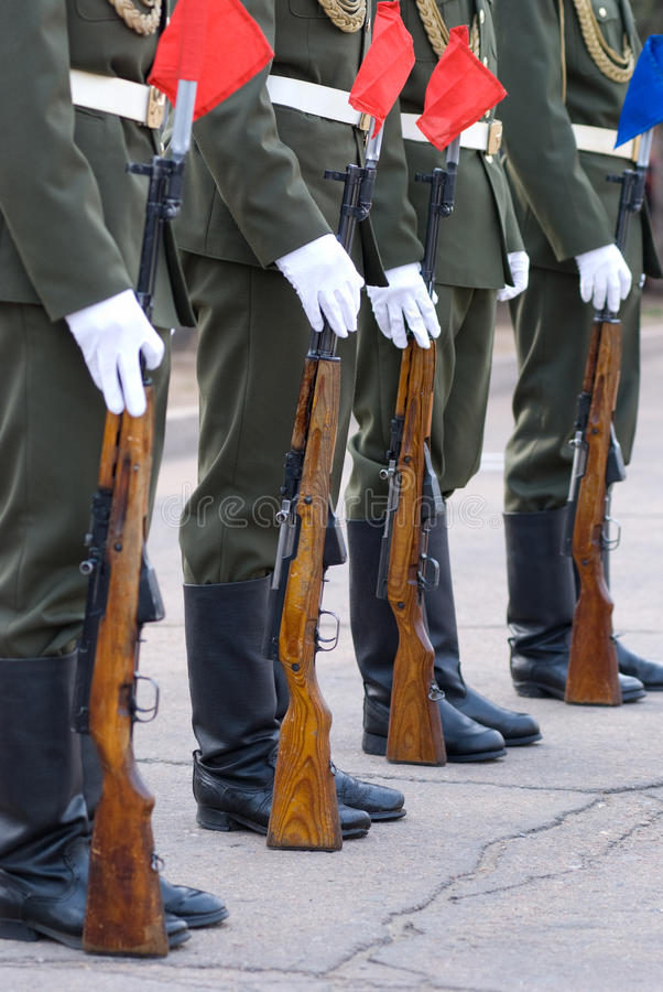 Guard of honour. Line of soldiers in full dress with their guns beside - lower half stock photos