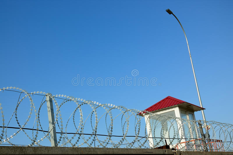 Guard tower. With barbed wire on a background of blue sky stock images