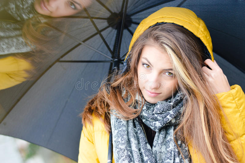 Guarda-chuva bonito da mulher no revestimento amarelo morno imagens de stock royalty free