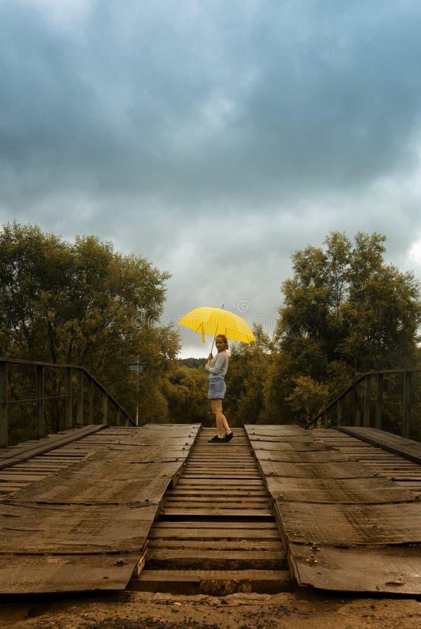 Guarda-chuva bonito do amarelo da posse da mulher e passeio em uma ponte velha no campo sob a chuva fotos de stock royalty free