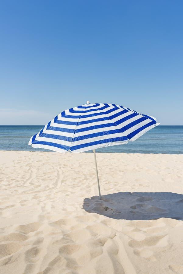 Guarda-chuva branco e azul só da tira na praia imagens de stock royalty free