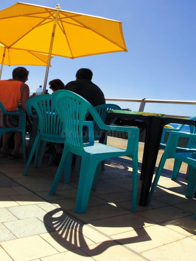 Guarda-chuva da cadeira de tabela da praia do café da parte dianteira de mar imagens de stock royalty free