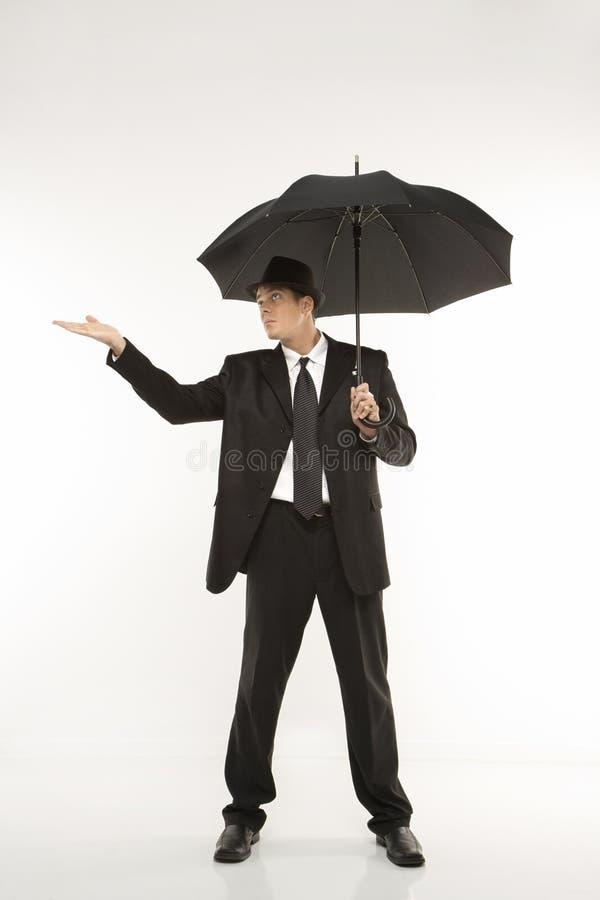 Guarda-chuva da terra arrendada do homem de negócios com à mão para fora. imagem de stock royalty free