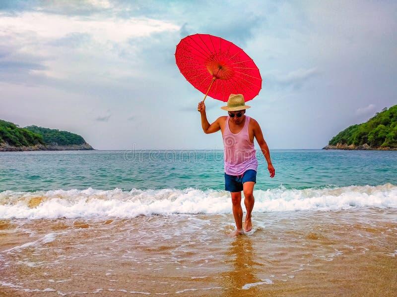 Guarda-chuva da terra arrendada do homem em uma praia Férias e curso tropicais fotos de stock