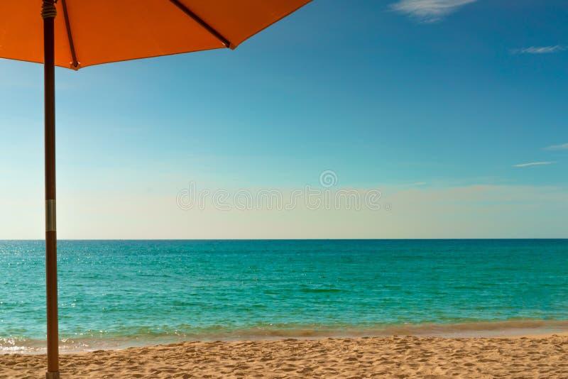 Guarda-chuva de praia alaranjado na praia dourada da areia pelo mar com água do mar verde esmeralda e as nuvens azuis do céu e as foto de stock
