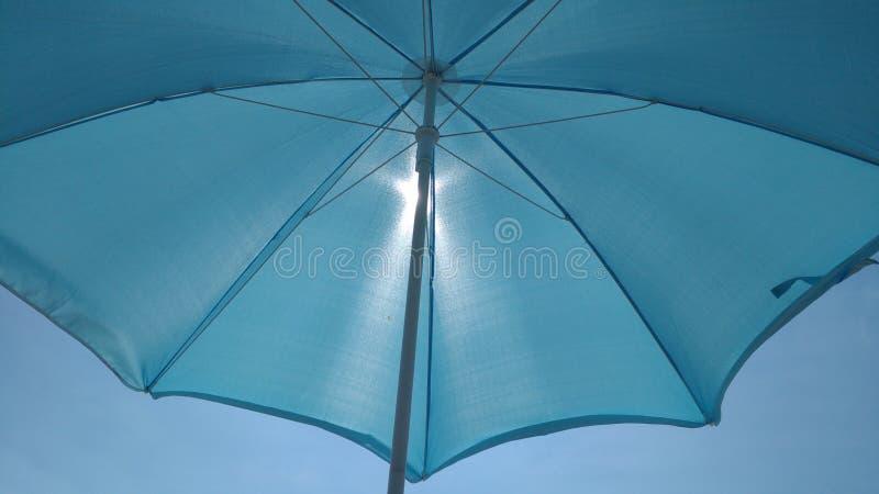 Guarda-chuva de praia com o sol atrás dele fotos de stock