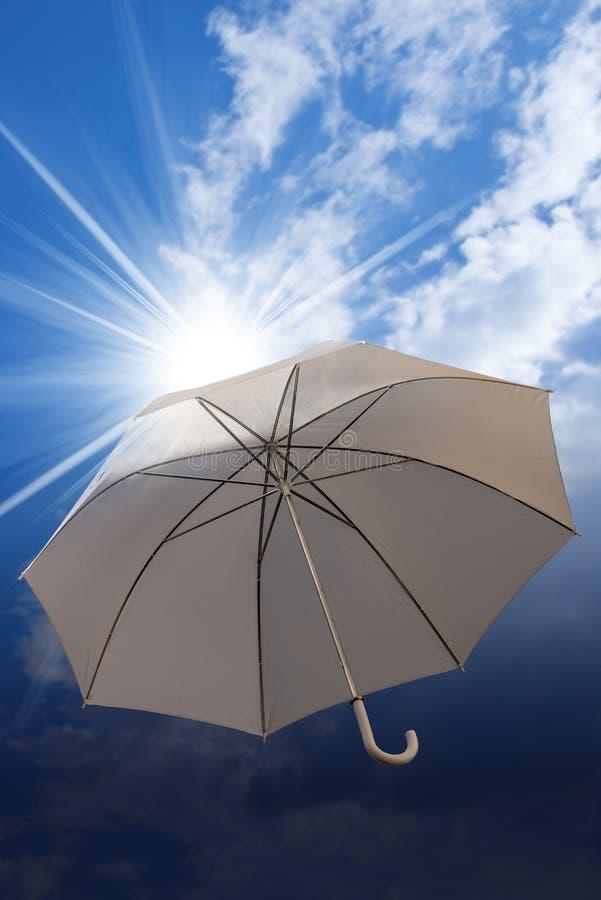 Guarda-chuva em um céu azul com nuvens e raios do sol imagens de stock