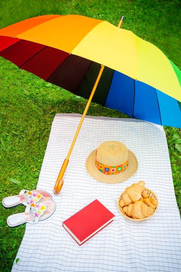 Guarda-chuva, livro, chapéu, sapatas e croissant do arco-íris imagens de stock