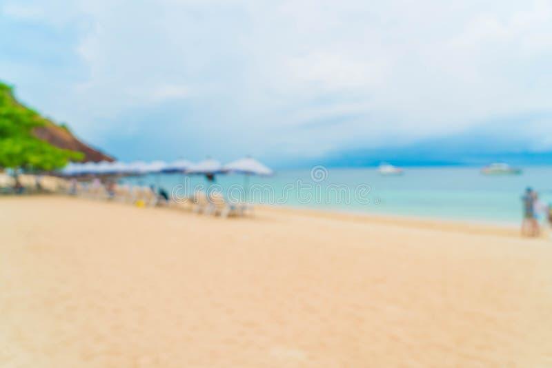 guarda-chuva luxuoso bonito e cadeira do borrão abstrato no mar e no bea foto de stock