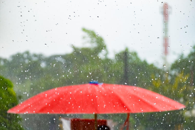 Guarda-chuva vermelho com chuva da queda da tempestade foto de stock royalty free