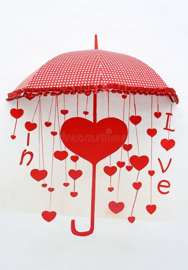 Guarda-chuva vermelho da decoração criativa com palavra da pintura ''no amor ''lugar na parede do cimento branco imagens de stock royalty free