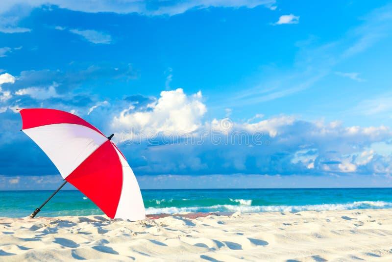 Guarda-chuva vermelho e branco colorido na praia do oceano com o céu azul e as nuvens bonitos Abrandamento, fundo idílico das fér imagens de stock royalty free
