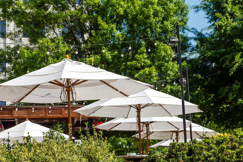 Guarda-chuvas brancos sobre o pátio do jardim imagem de stock royalty free
