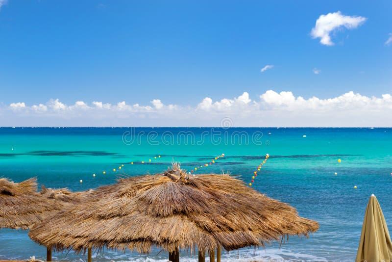 Guarda-chuvas cobridos com sapê no café da praia Bali, Creta foto de stock royalty free