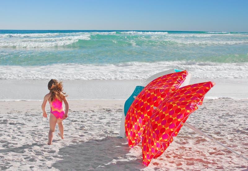 Guarda-chuvas da menina e de praia imagens de stock
