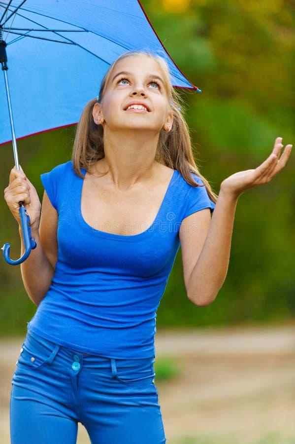 Guarda-chuvas da terra arrendada da menina do adolescente fotografia de stock royalty free