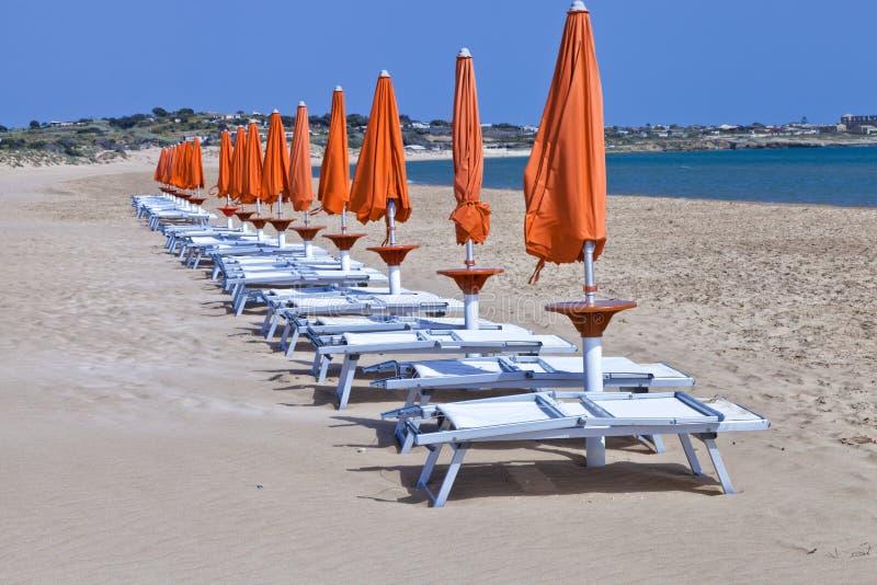 Guarda-chuvas de praia alaranjados de Sun com as cadeiras plásticas brancas imagens de stock royalty free