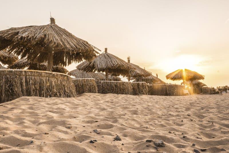 Guarda-chuvas de praia dos materiais naturais pelo mar na areia imagem de stock