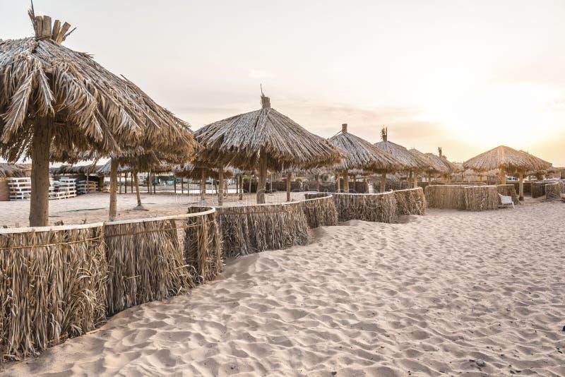 Guarda-chuvas de praia dos materiais naturais pelo mar na areia fotos de stock