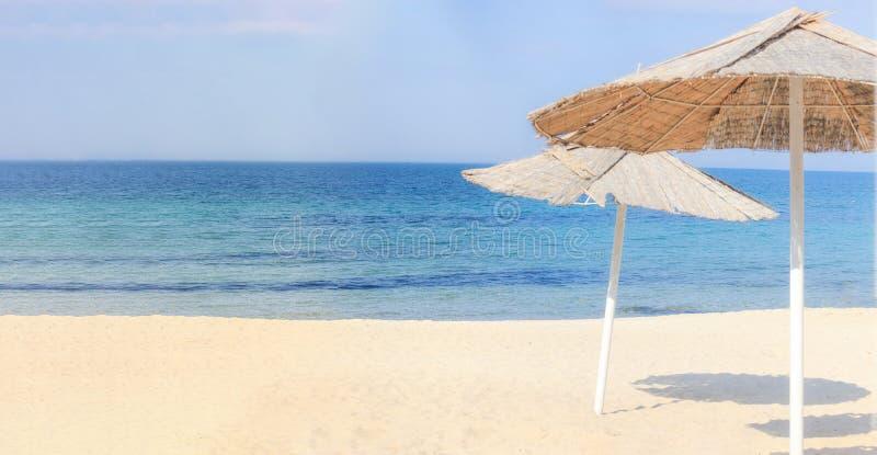 Guarda-chuvas de praia e areia limpa contra imagens de stock