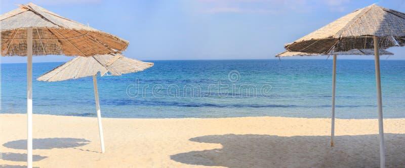 Guarda-chuvas de praia e areia limpa contra imagens de stock royalty free