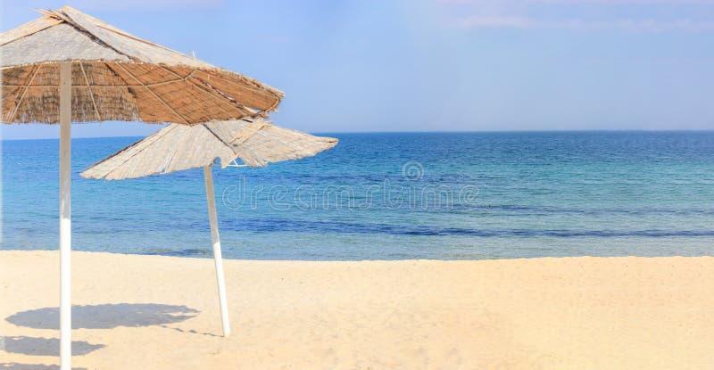 Guarda-chuvas de praia e areia limpa contra fotos de stock