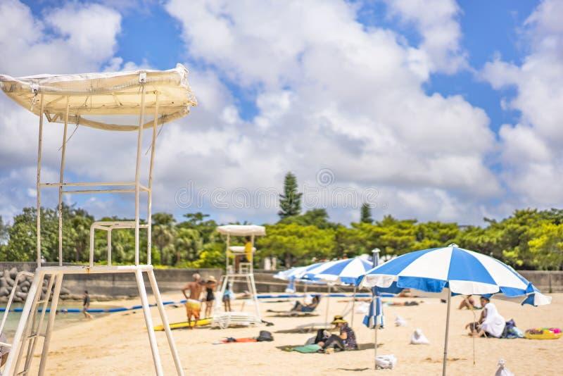 Guarda-chuvas de praia e cadeiras da salva-vidas no Sandy Beach Naminoue em Naha City em Okinawa Prefecture, Japão foto de stock royalty free