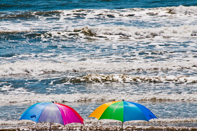 Guarda-chuvas de praia e ondas de oceano causando um crash imagem de stock
