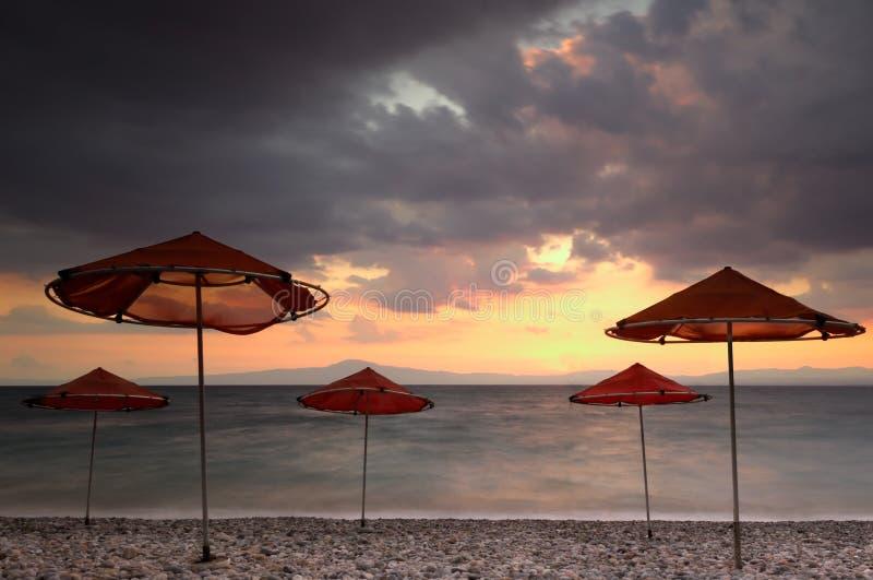 Guarda-chuvas de praia em um dia ventoso imagens de stock