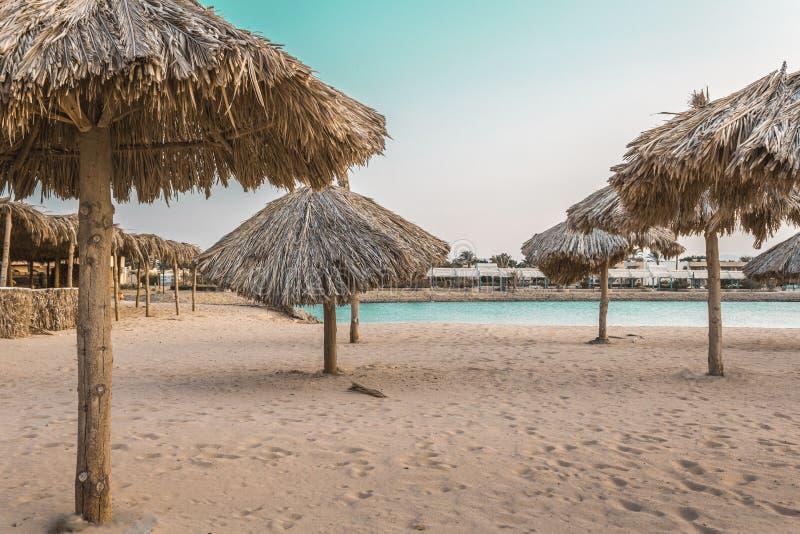 Guarda-chuvas de praia feitos dos materiais naturais pelo mar fotografia de stock royalty free