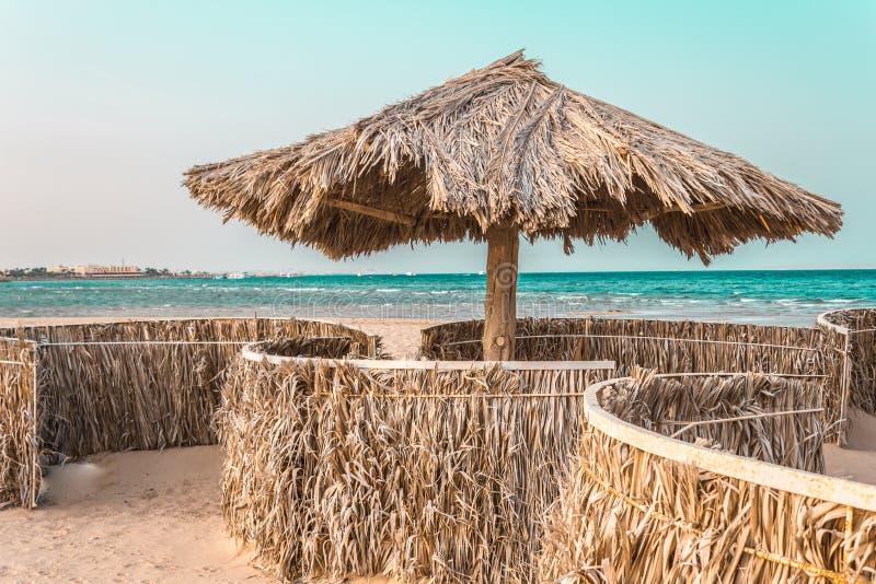Guarda-chuvas de praia feitos dos materiais naturais pelo mar fotos de stock