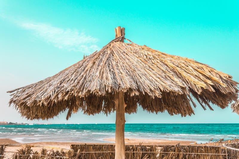 Guarda-chuvas de praia feitos dos materiais naturais pelo mar fotos de stock royalty free