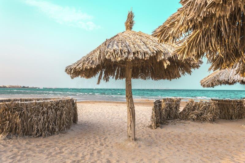 Guarda-chuvas de praia feitos dos materiais naturais pelo mar imagens de stock royalty free