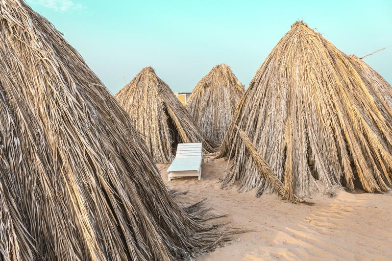 Guarda-chuvas de praia feitos dos materiais naturais pelo mar imagem de stock