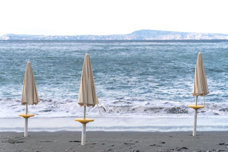 Guarda-chuvas de praia na perspectiva das ondas fortes imagens de stock