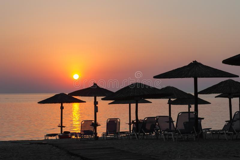 Guarda-chuvas de praia no por do sol, com sunbeds, por do sol quente na praia imagem de stock