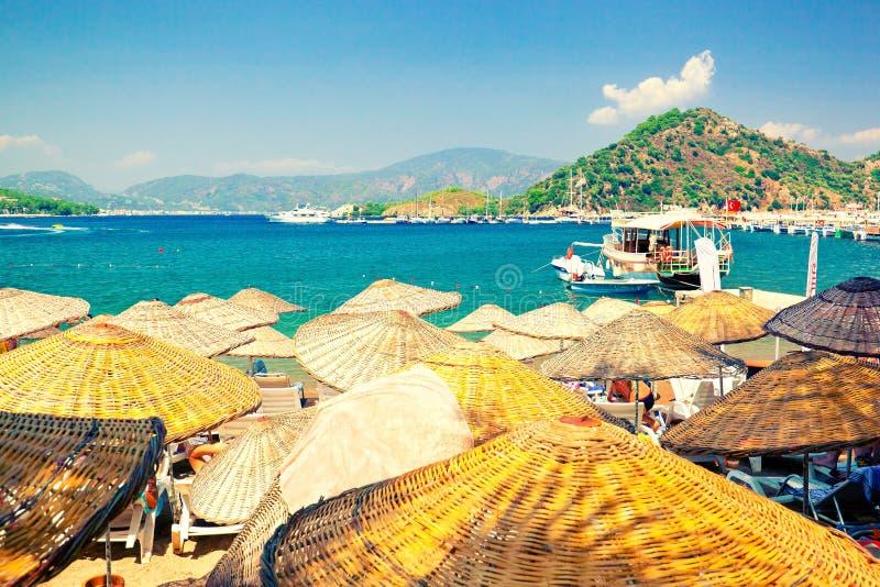 Guarda-chuvas de praia de vime pitorescos na praia ensolarada de riviera turco imagens de stock