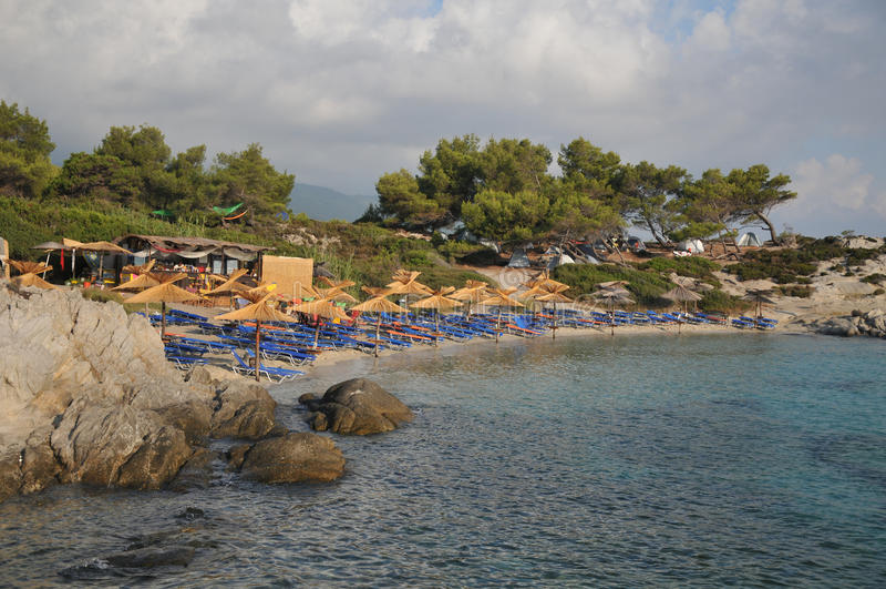 Guarda-chuvas e cadeiras de plataforma na praia arenosa imagem de stock royalty free