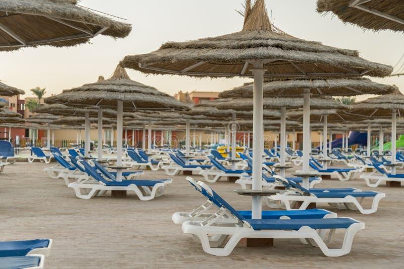 Guarda-chuvas e salas de estar do chaise na praia Vista cênico do Sandy Beach privado com as camas do sol do mar foto de stock