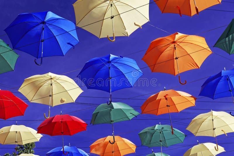 guarda-chuvas Multi-coloridos no céu acima da rua Guarda-chuvas de flutuação da aleia fotos de stock royalty free