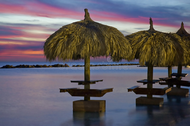 Guarda-chuvas no oceano no por do sol imagem de stock